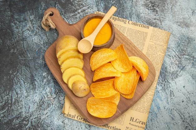Boven weergave van lekkere zelfgemaakte chips gesneden aardappelschijfjes op houten snijplank op krant op grijze tafel