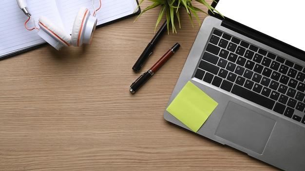 Boven weergave van mock-up computerlaptop, hoofdtelefoon, notebook, pennen en plant op houten tafel.