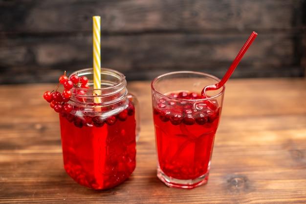 Boven weergave van natuurlijk biologisch vers bessensap in een glas en een fles geserveerd met buizen op een houten tafel