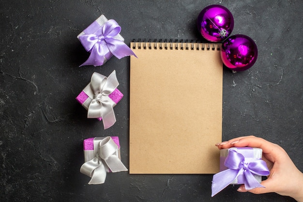 Boven weergave van nieuwjaarsversieringen en notitieboekje met geschenken op zwarte achtergrond