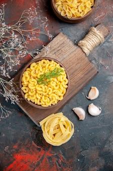 Boven weergave van ongekookte pasta's in een bruine kom en knoflook op houten snijplank op gemengde kleurentafel
