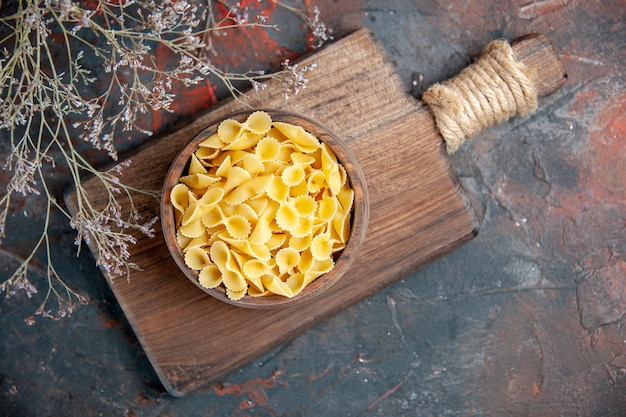 Boven weergave van ongekookte pasta's in een bruine kom op houten snijplank op gemengde kleurentafel