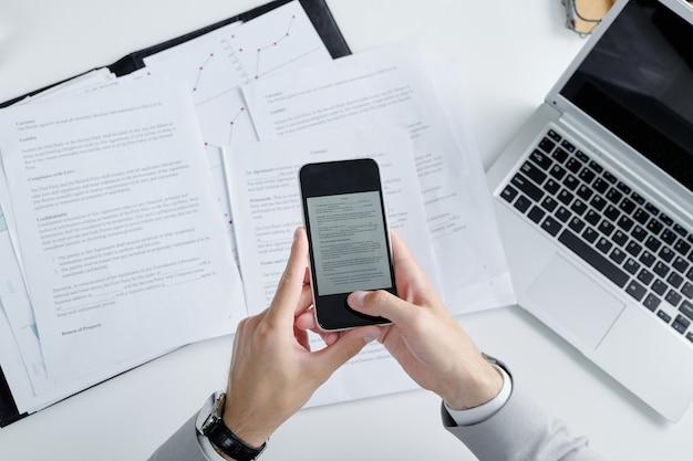 Boven weergave van onherkenbare advocaat die smartphone gebruikt tijdens het fotograferen van contractpapieren op tafel