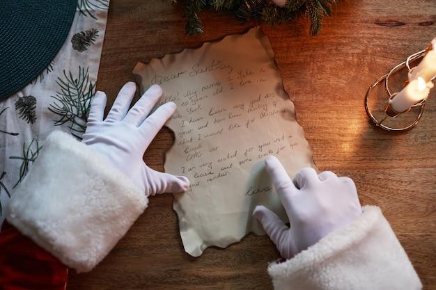 Boven weergave van onherkenbare kerstman in witte handschoenen die vinger onder woorden laten lopen tijdens het lezen van...