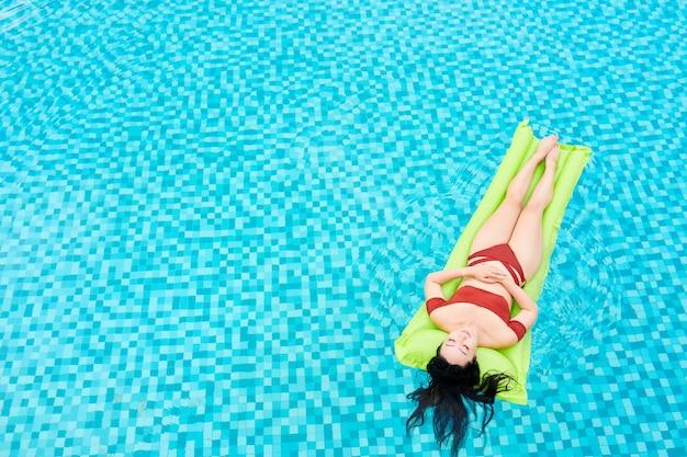Boven weergave van ontspannen jonge aziatische vrouw liggend op opblaasbare matras tijdens het zwemmen in het zwembad