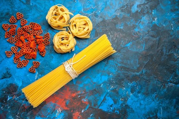 Boven weergave van pasta noedels aan de rechterkant op blauwe achtergrond
