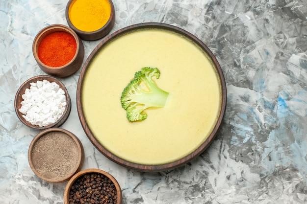 Boven weergave van romige broccolisoep in een bruine kom en verschillende kruiden op grijze tafel