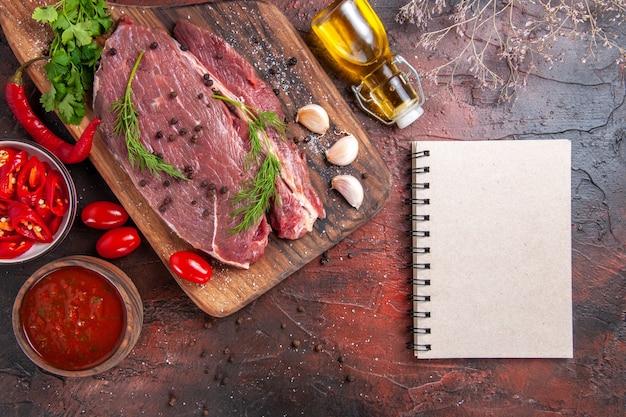Boven weergave van rood vlees op houten snijplank knoflook groene gehakte peper gevallen oliefles en notitieboekje op donkere achtergrond