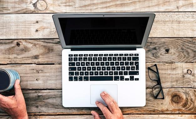 Boven weergave van senior bebaarde man met een kopje koffie met toetsenbord met laptop surfen op het net of werken, houten rustieke tafel buiten op terras