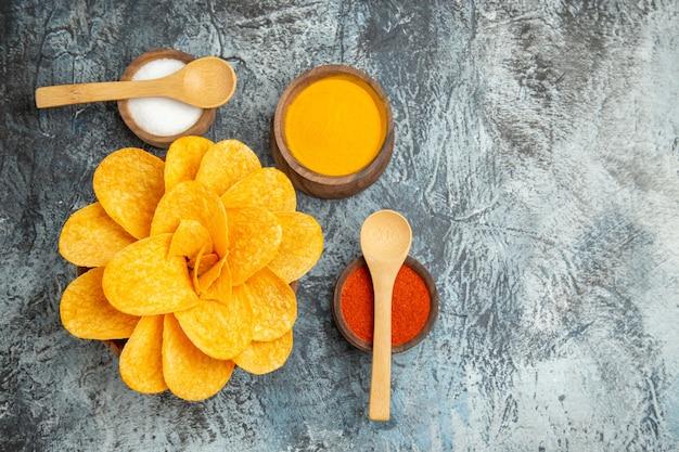 Boven weergave van smakelijke aardappelchips ingericht als bloemvormige verschillende kruiden met lepels erop en notebook op grijze tafel