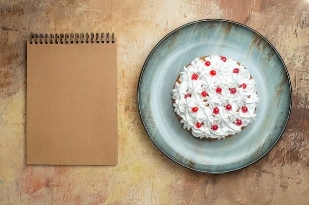 Boven weergave van smakelijke cake versierd met room en bessen op een blauw bord en spiraalvormig notitieboekje op een kleurrijke tafel