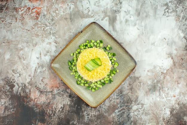 Boven weergave van smakelijke salade geserveerd met gehakte komkommer op gemengde kleur achtergrond