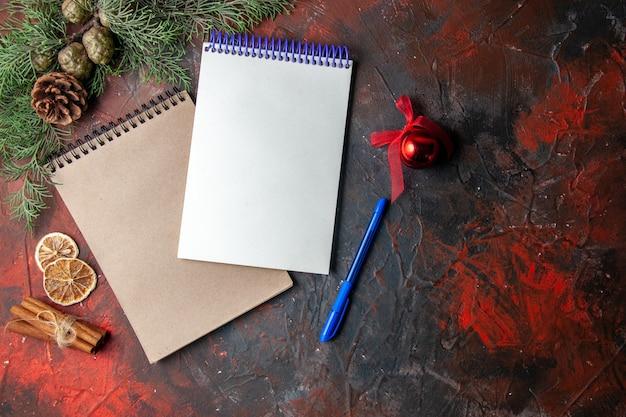Boven weergave van spiraalvormige notitieboekjes en pen spar tak kaneel limoenen conifer kegel op donkere achtergrond