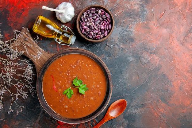 Boven weergave van tomatensoep op een bruine snijplank op een tafel met gemengde kleuren
