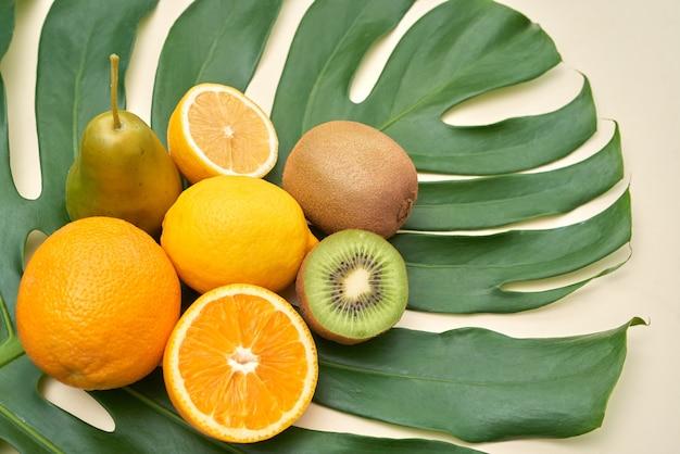 Boven weergave van vers rijp fruit zoals citroen, sinaasappel, peer, kiwi op tropisch blad