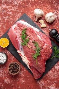 Boven weergave van vers rood vlees met groen en peper op zwarte bord mes knoflook citroen kruiden houten hamer citroen op olie pastel rode achtergrond