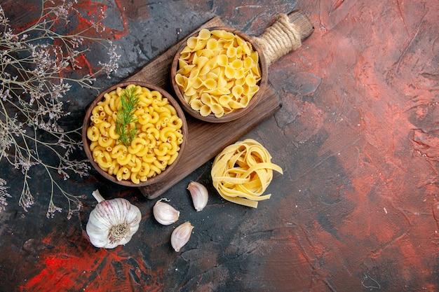 Boven weergave van verschillende soorten ongekookte pasta's op houten snijplank en knoflook op gemengde kleurentafel