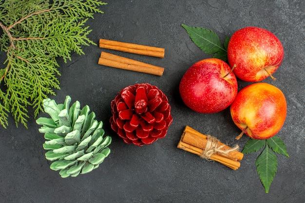 Boven weergave van verse appels, kaneellimoenen en decoratieaccessoires op zwarte achtergrond
