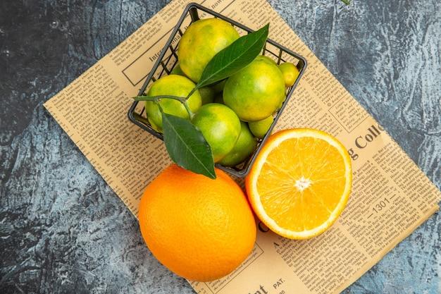 Boven weergave van verse citroenen binnen en buiten een mand op krant op grijze achtergrond