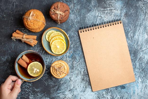 Boven weergave van verse citroenen en hand met een kopje zwarte thee met kaneel