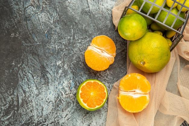 Boven weergave van verse citroenen in een gevallen zwarte mand op handdoek op grijze tafelbeelden