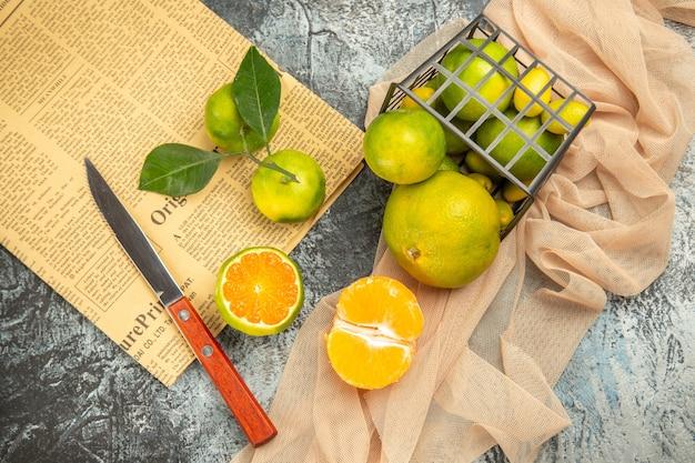 Boven weergave van verse citroenen in een gevallen zwarte mand op handdoekmes en krant op grijze tafel