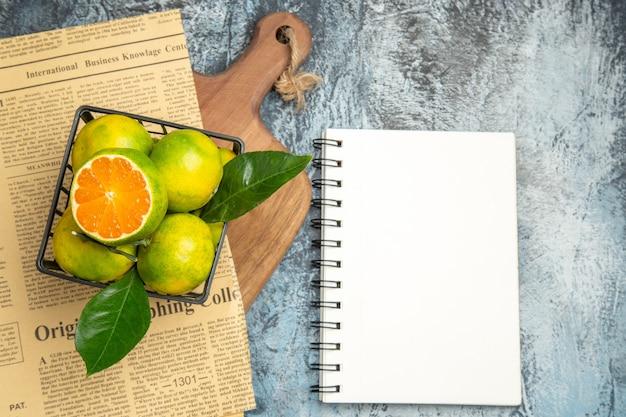 Boven weergave van verse citrusvruchten krant op houten snijplank en notebook op grijze achtergrond