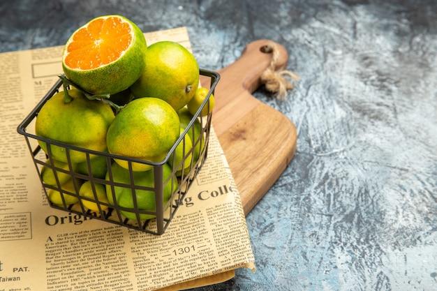 Boven weergave van verse citrusvruchten krant op houten snijplank op grijze achtergrond