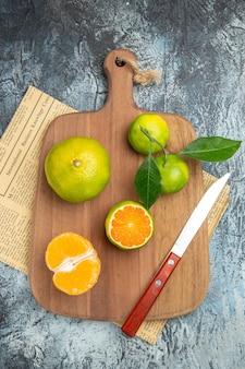 Boven weergave van verse citrusvruchten met bladeren op houten snijplank in halve vormen gesneden en mes op krant op grijze achtergrond