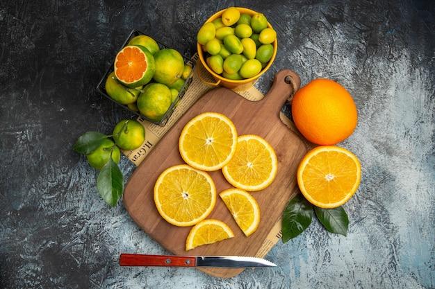 Boven weergave van verse citrusvruchten met mes op houten snijplank op krant op grijze achtergrond