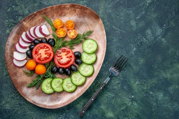 Boven weergave van verse gehakte groenten olijven in een bruine plaat en vork op groen zwart gemengde kleuren tafel