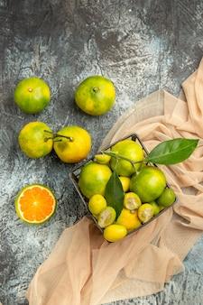 Boven weergave van verse kumquats en citroenen in een zwarte mand op een handdoek en vier citroenen op een grijze achtergrond