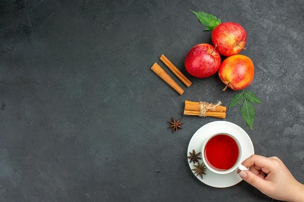 Boven weergave van verse natuurlijke biologische rode appels met groene bladeren, kaneellimoenen en een kopje thee op zwarte achtergrond