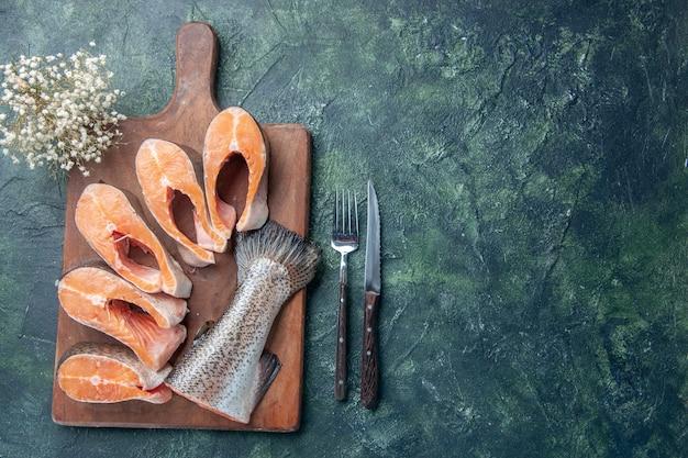 Boven weergave van verse rauwe vis op houten snijplank en mes aan de rechterkant op donkere mix kleuren tafel met vrije ruimte