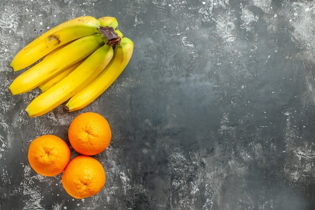 Boven weergave van verse sinaasappels en natuurlijke biologische bananenbundel aan de rechterkant donkere achtergrond