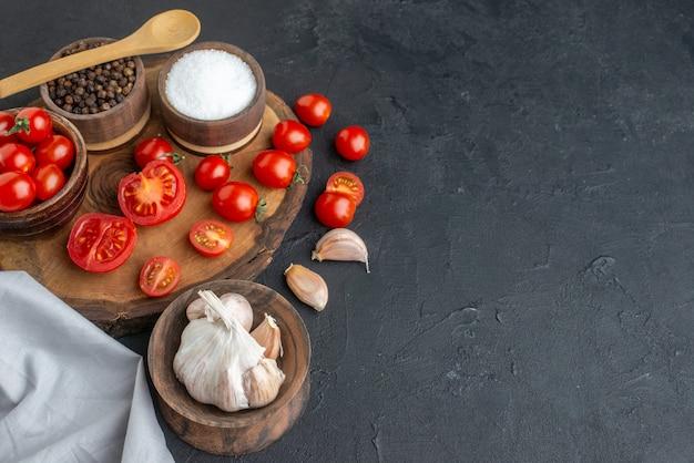 Boven weergave van verse tomaten en kruiden op houten plank witte handdoek knoflook op zwarte ondergrond
