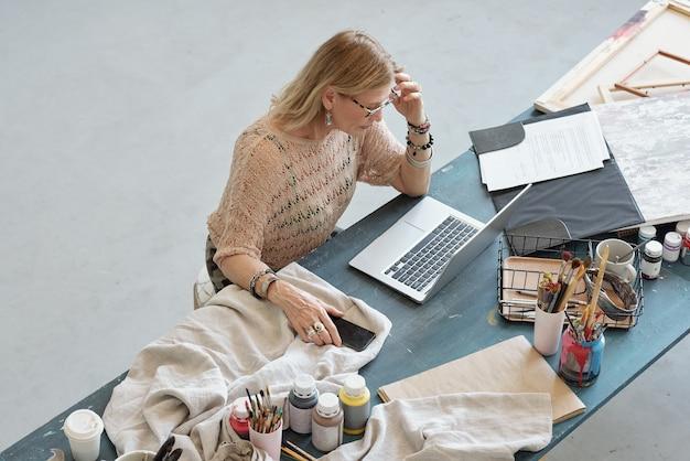 Boven weergave van volwassen kunstenaar gericht op kunst techniek artikel zittend aan een bureau en met behulp van laptop