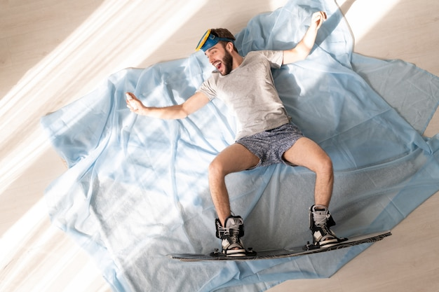 Boven weergave van vrolijke jonge bebaarde man in slipje en t-shirt liggend met uitgestrekte armen op lakens terwijl hij doet alsof hij snowboard thuis isolatie