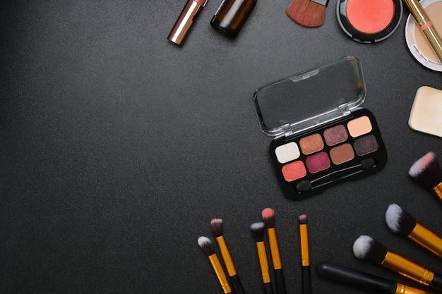 Boven weergave van vrouwelijk bureau met lippenstift, oogpalet, gezichtspoeder, borstels en kopieerruimte op donkere achtergrond.
