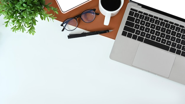 Boven weergave van wit bureau met laptop, bril, kamerplant, koffiekopje en notebook.