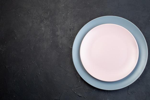 Boven weergave van witte en blauwe keramische lege platen op zwarte achtergrond met vrije ruimte