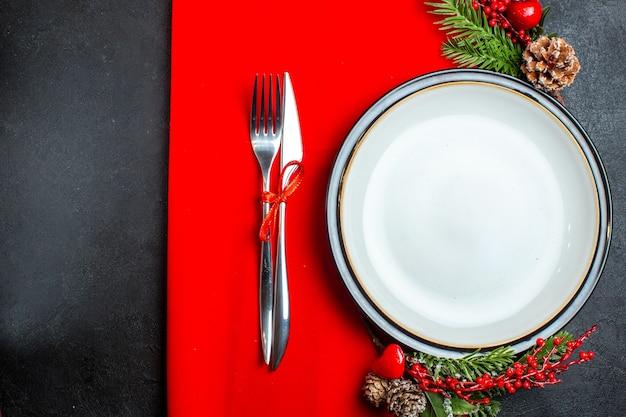 Boven weergave van xsmas achtergrond met dinerbord decoratie accessoires fir takken en bestek op een rood servet