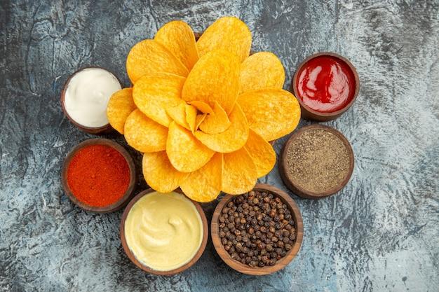Boven weergave van zelfgemaakte aardappelchips versierd als bloemvormige mayonaise en ketchup op grijze tafel