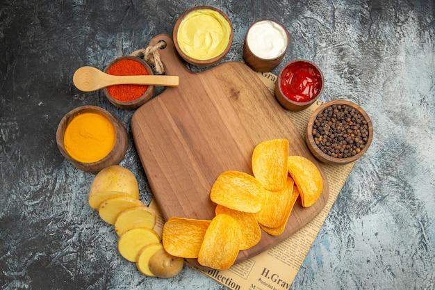 Boven weergave van zelfgemaakte heerlijke aardappelchips op houten snijplank verschillende kruiden en smaken op krant op grijze tafel