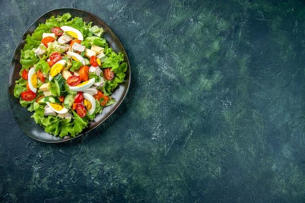 Boven weergave van zelfgemaakte heerlijke salade in een zwarte plaat aan de rechterkant op groen zwart mix kleuren tafel met vrije ruimte