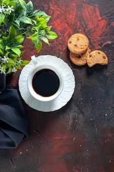 Boven weergave van zelfgemaakte heerlijke suikerkoekjes en bloempot een kopje koffie op donkere mixkleuren achtergrond