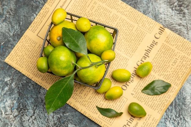 Boven weergave van zwarte mand met verse groene mandarijnen en kumquats op kranten op grijze achtergrond