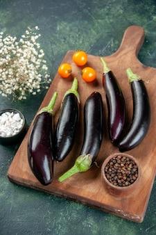 Boven weergave zwarte aubergines op de donkere achtergrond van de snijplank