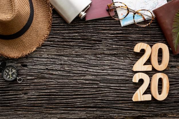 Bovenaanzicht 2020 gelukkig nieuwjaarsnummer op houten tafel met avontuurlijk accessoire