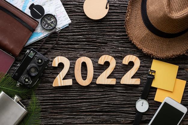 Bovenaanzicht 2022 gelukkig nieuwjaar nummer op houten tafel met avontuur accessoire item, vakantieplanning.